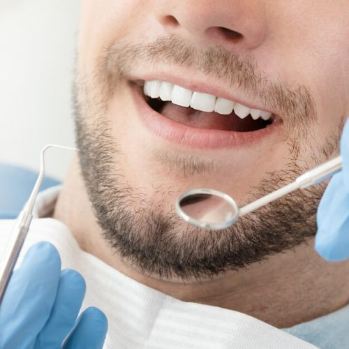 Young man opening his mouth during a dental treatment with tools about to enter