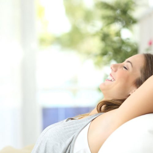 smiling woman relaxing at home on couch with arms crossed behind head