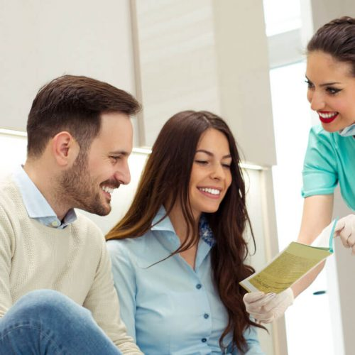 dental staff explaining information from a brochure to a young professional couple
